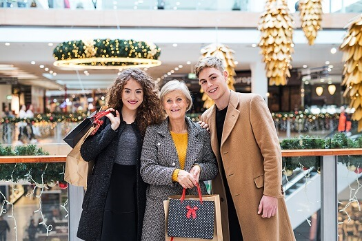 A portrait of grandmother and teenage grandchildren in shopping center at Christmas